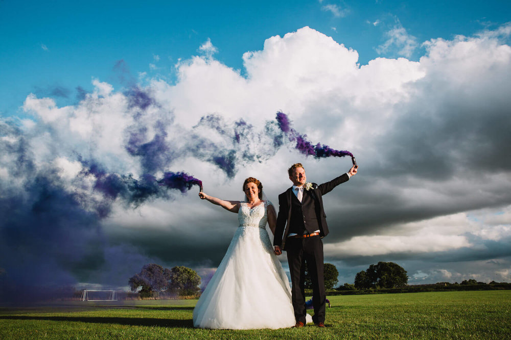 newly wedded couple holding purple smoke grenades in a sports field