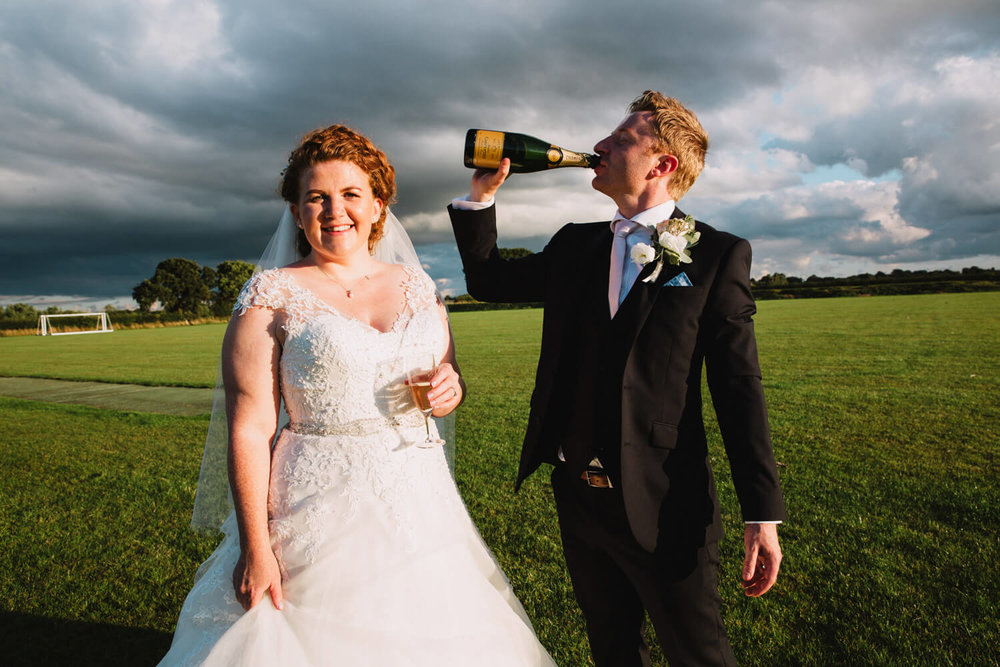 groom drinking champagne from the bottle