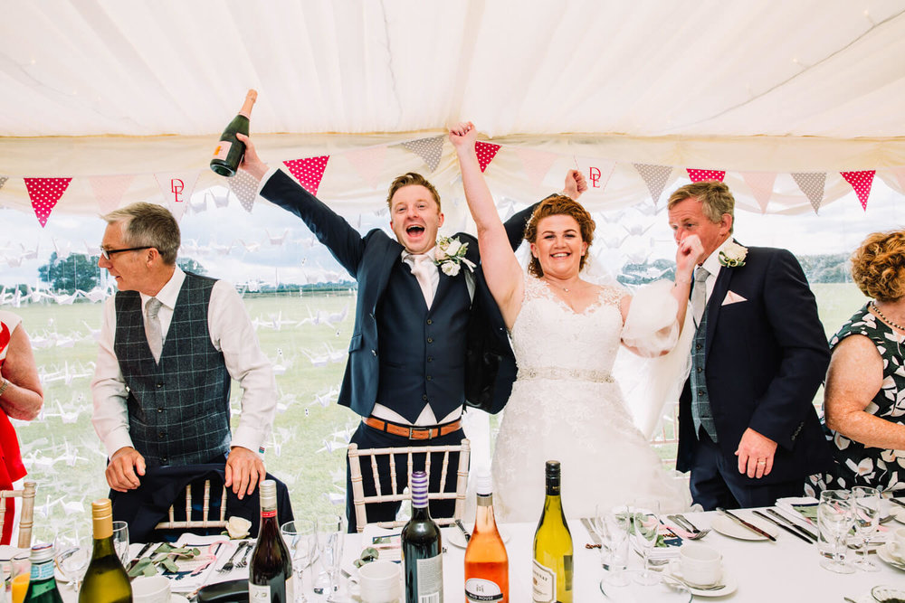 newlyweds celebrating at top table with bottle of champagne