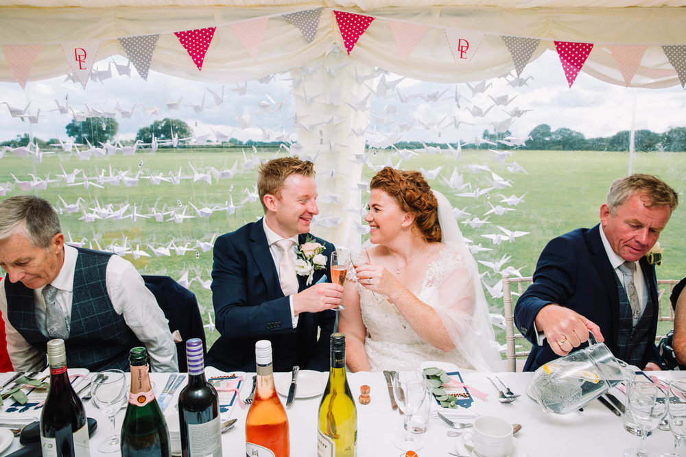 bride and groom clinking champagne flutes on top table