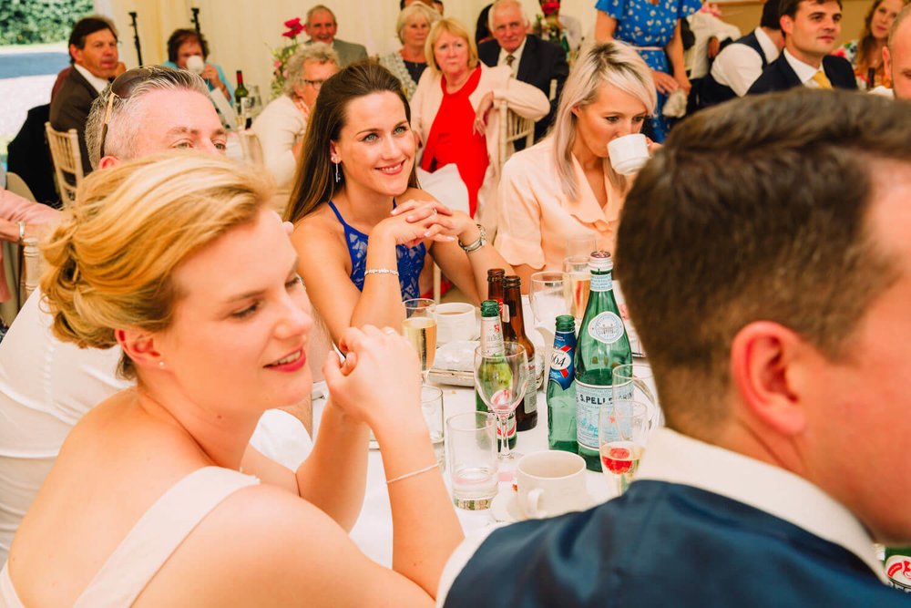 Wedding guests laughing while listening to speeches