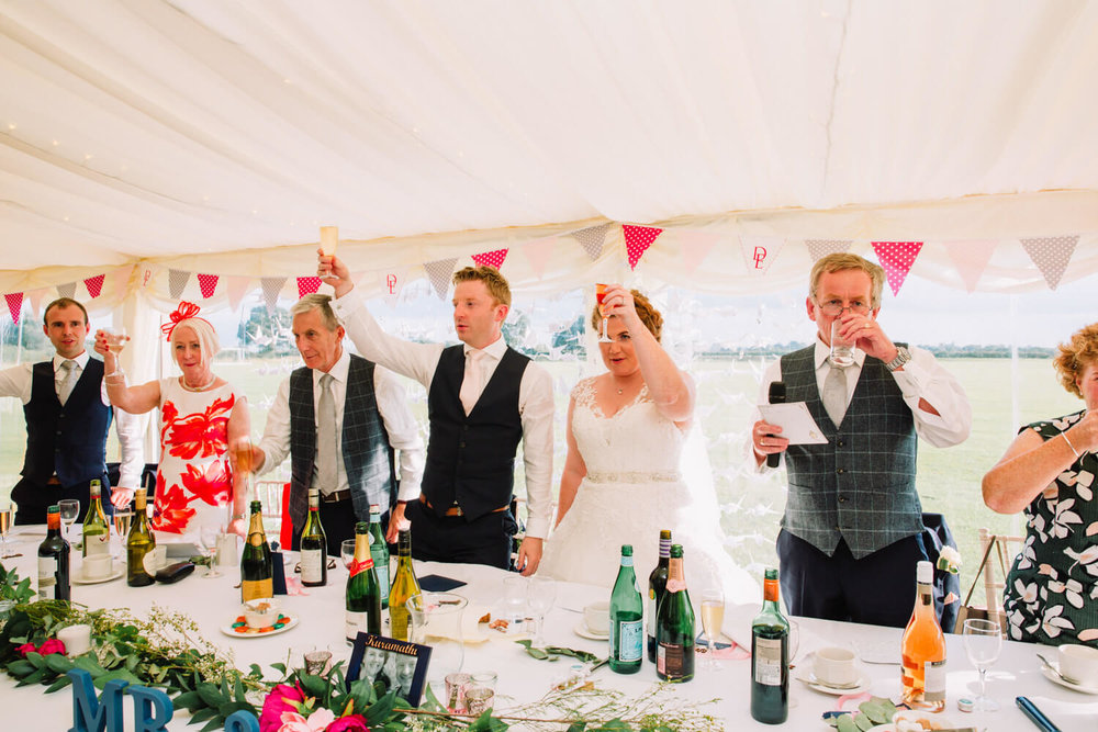 bride and groom raising a toast with top table families and friends