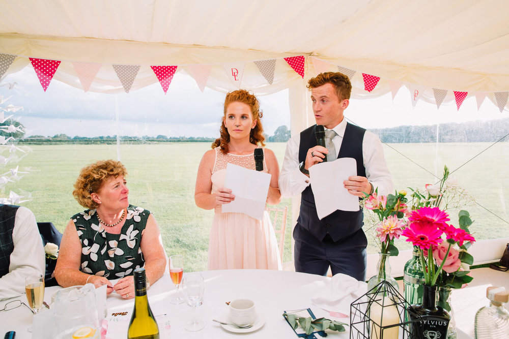 best man and bridesmaid giving speech to bride and groom