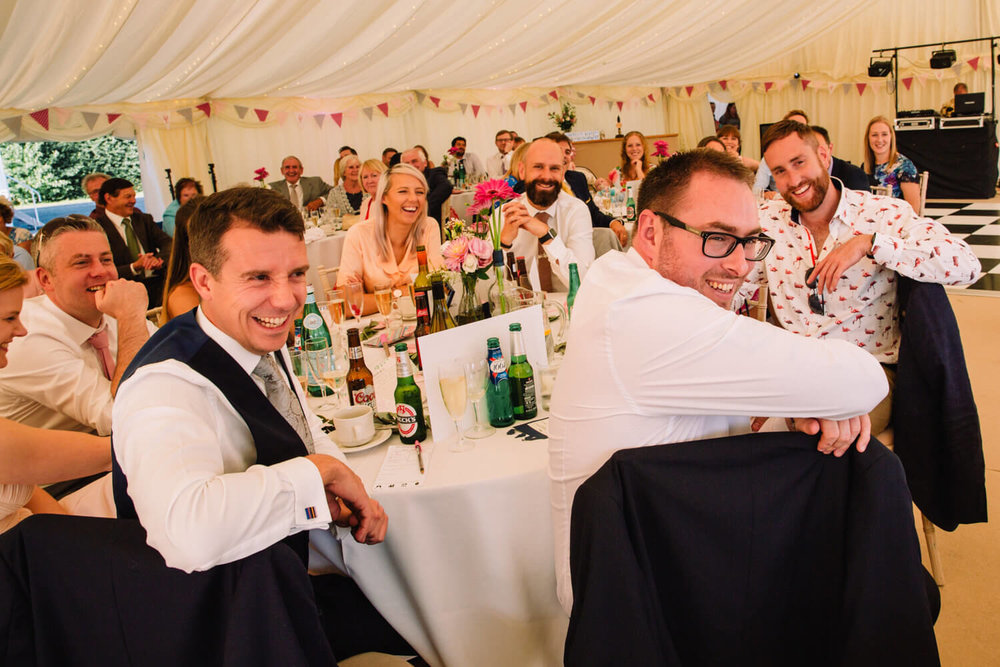 Wedding guests laughing around table