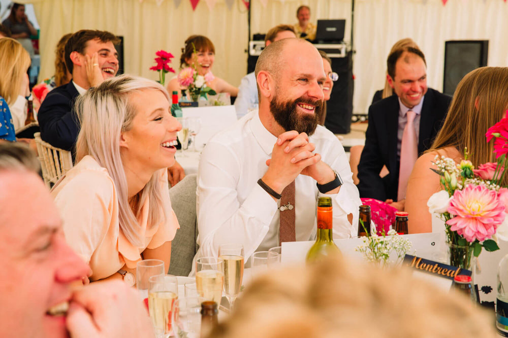 wedding guests sat at breakfast table laughing at speeches