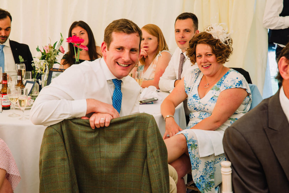 wedding guests sat on table laughing with each other