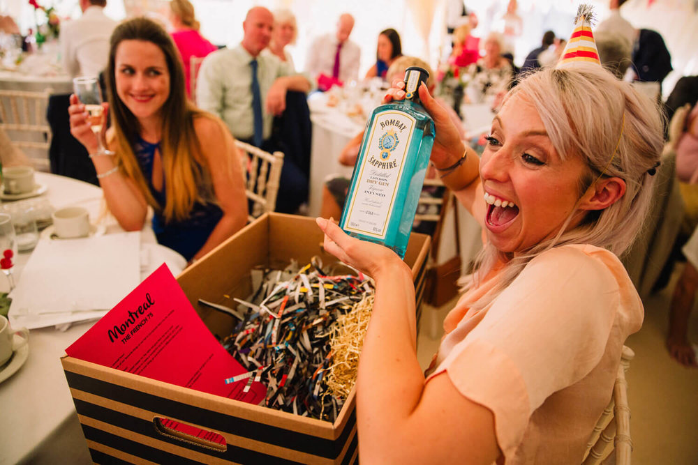 ecstatic look of guest when she pulls out bombay sapphire gin bottle