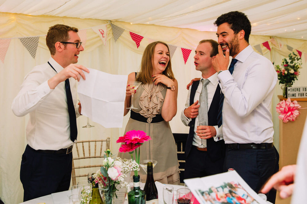 wedding guests hysterically laughing together
