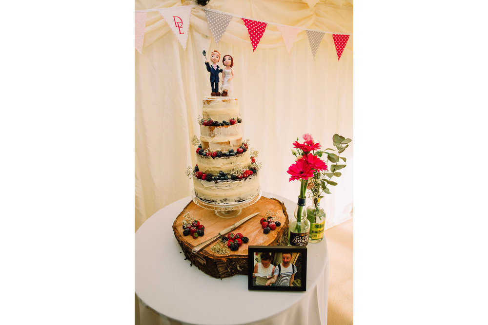 wedding cake sat on table with cake toppers sat on top