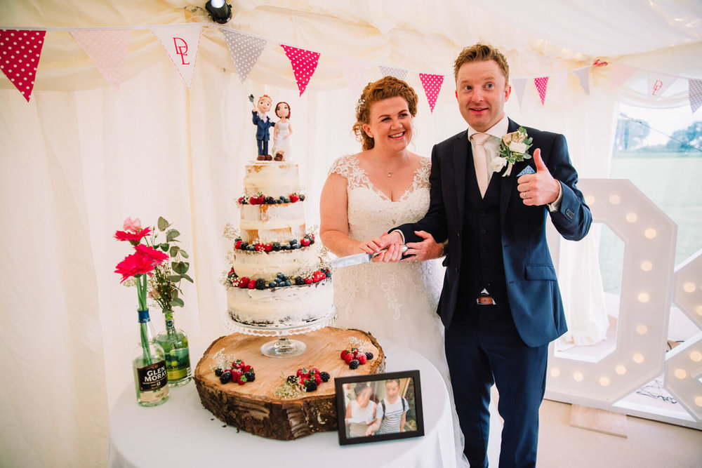 bride and groom cutting cake while giving a thumbs up to guests