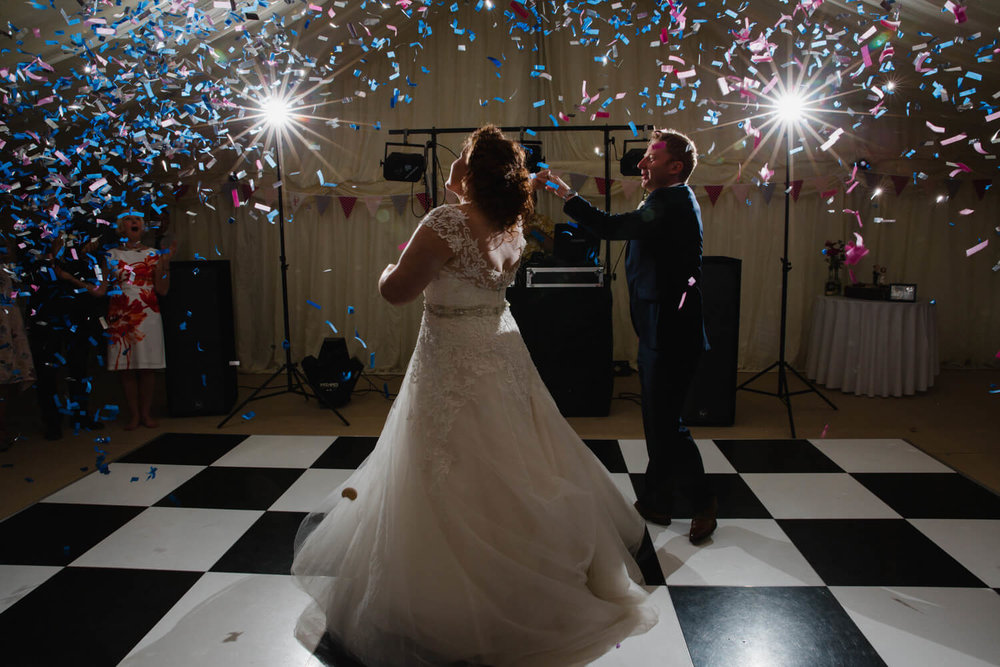 confetti canons shoot above bride and groom during first dance