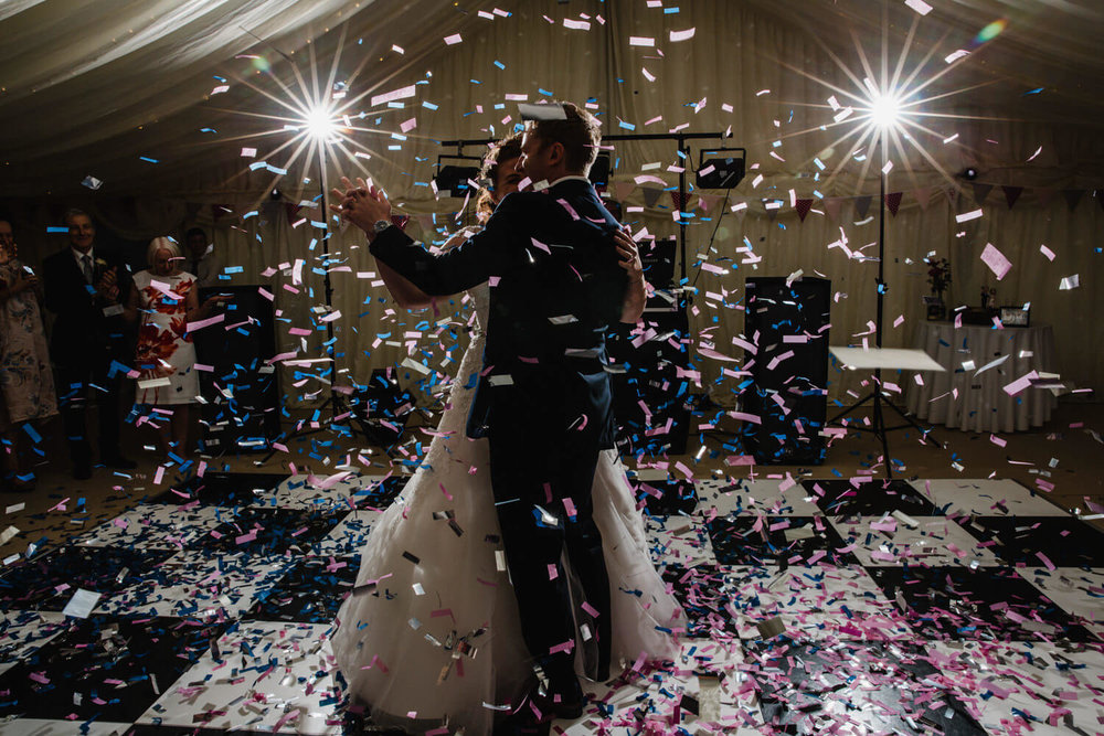 newlyweds dancing under confetti fired from cannon with pink and blue stands falling around couple