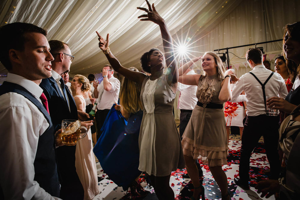 wedding guests throwing their arms up to music on the dance floor