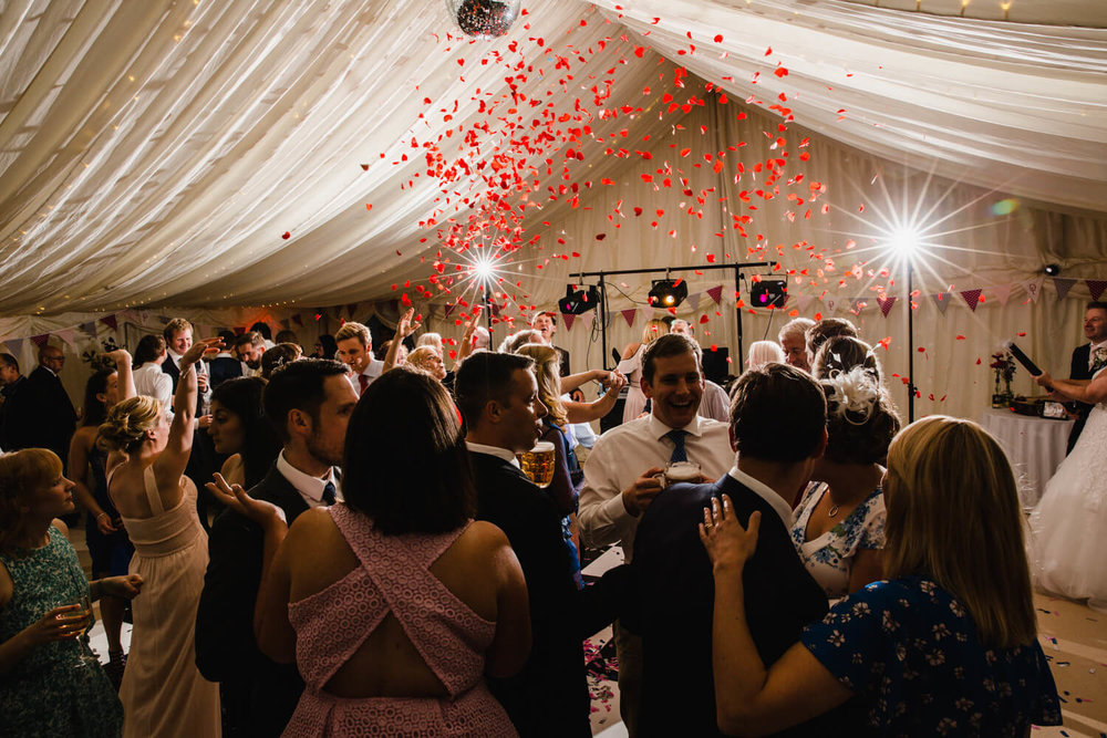 wedding party showered with red confetti on the dance floor