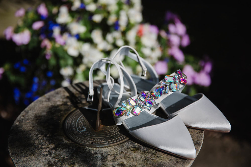 wedding shoes sparkling in the sun sat on sun-dial