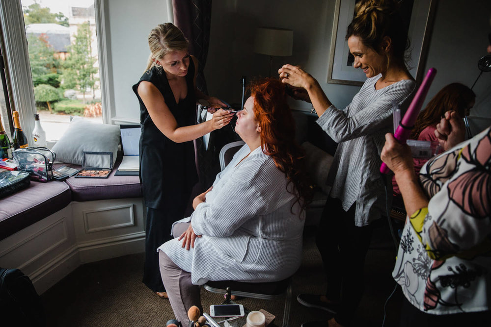 bride with bridesmaids having make up preparation in the window