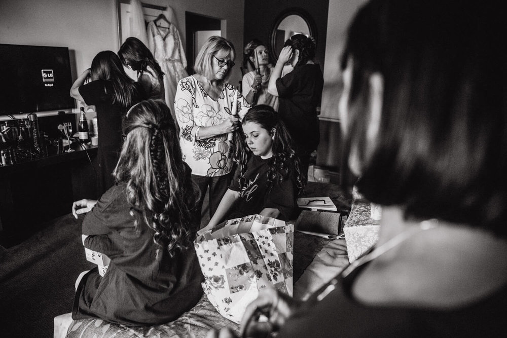 black and white wide angle photograph of bridal party having hair prepared