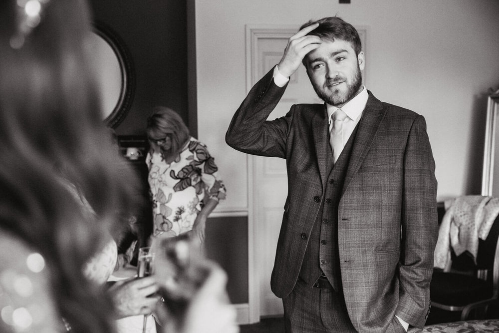 black and white photograph of best man fixing hairstyle