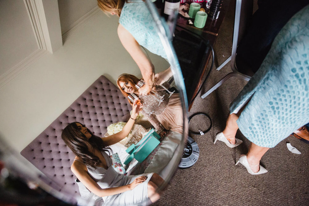 mirror reflection photograph of bridesmaids clinking champagne glasses
