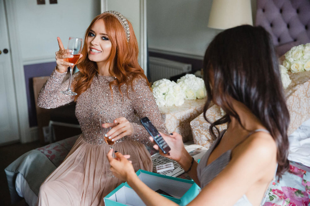 bridesmaid drinking champagne out of flute