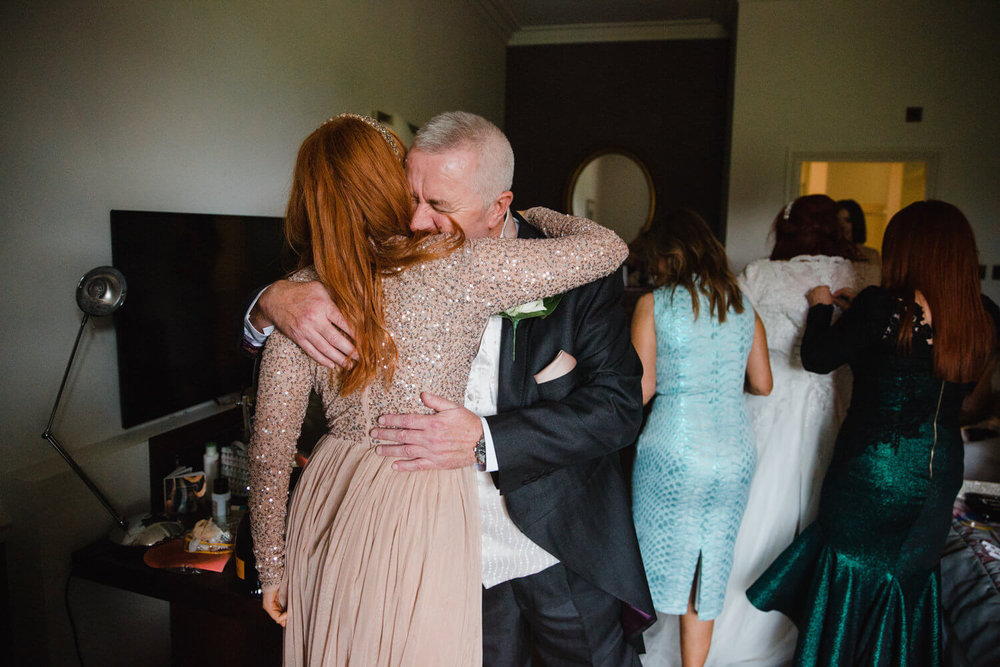 father of bride hugs daughter in intimate moment