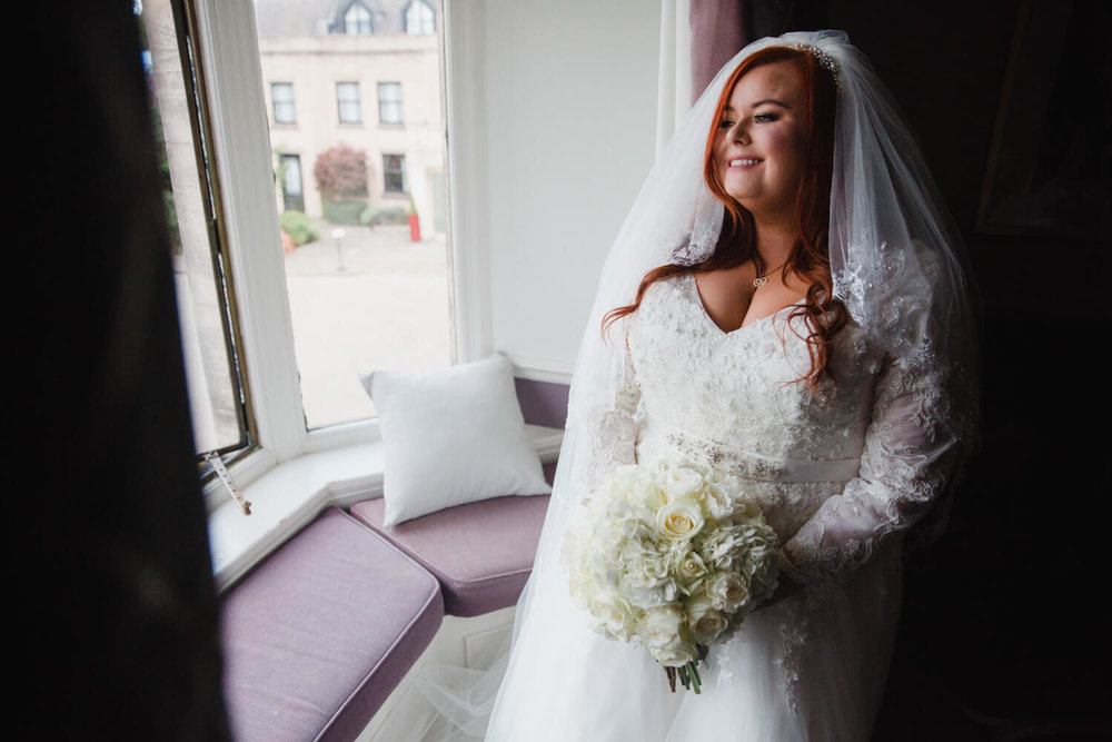 bride looking out of window holding bouquet for portrait