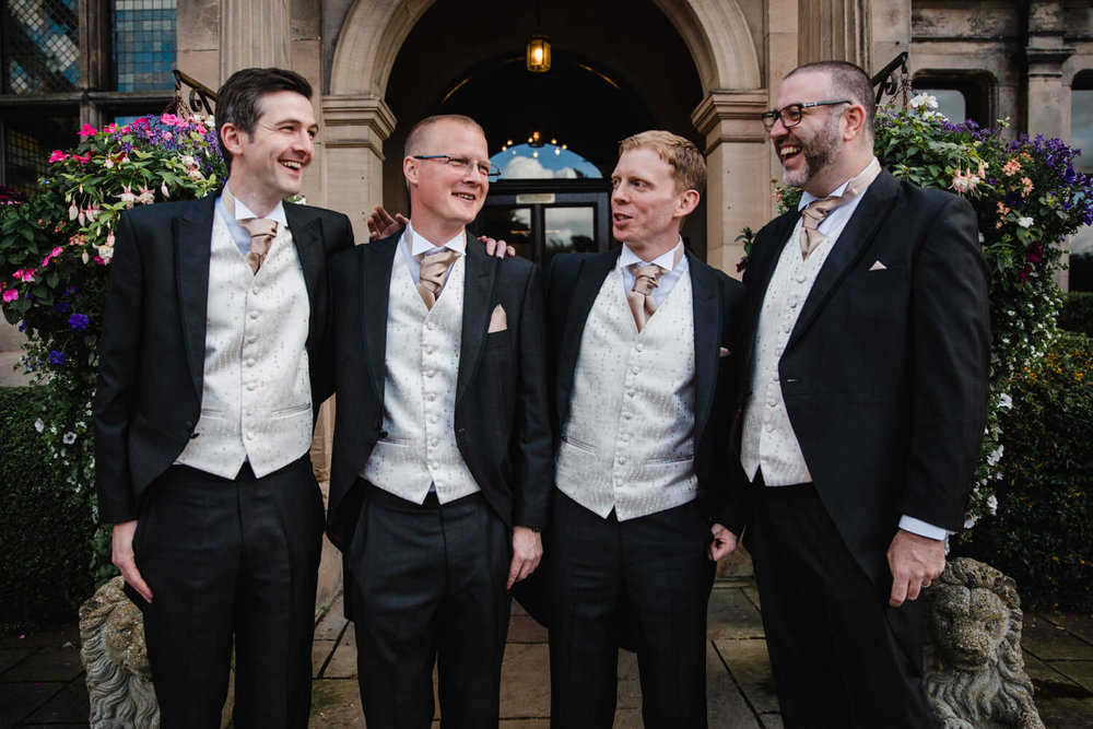 groomsmen sharing joke together before wedding ceremony