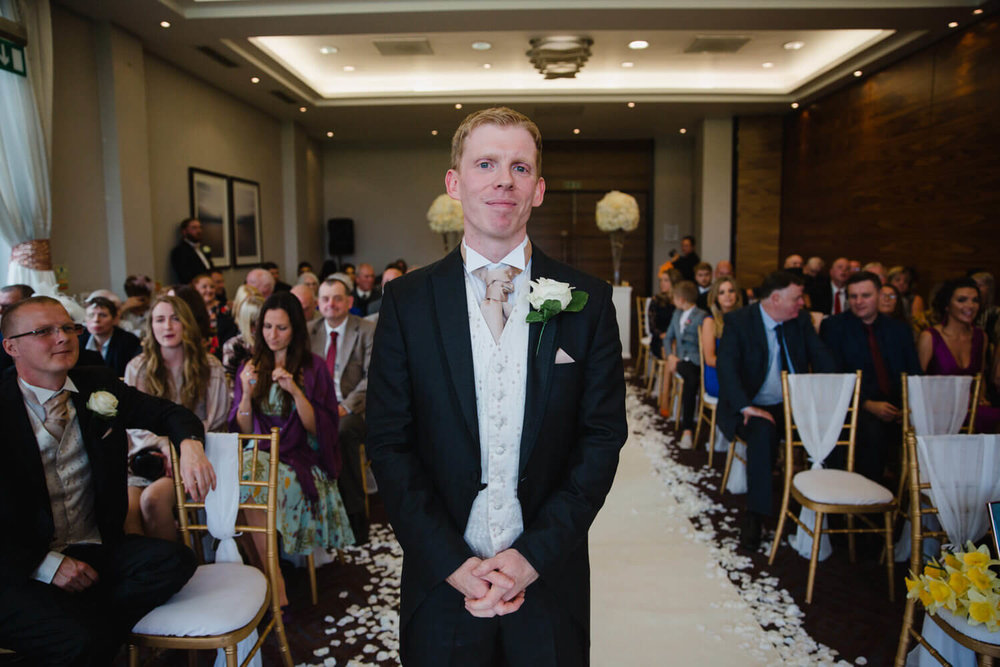 groom stood at top of aisle looking at camera before service begins