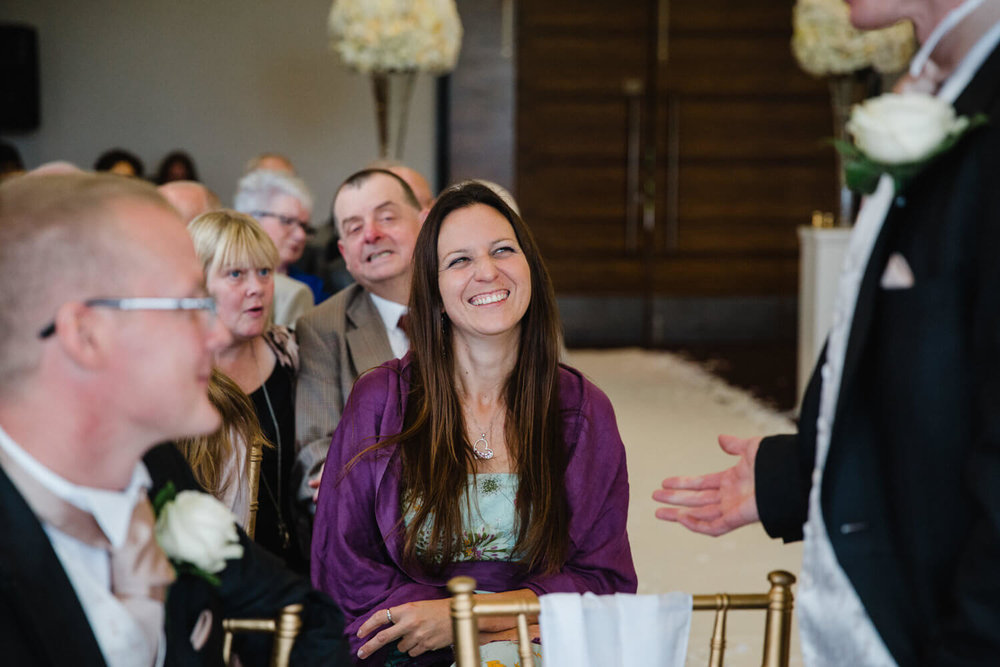 wedding guest sat next to aisle sharing joke with groom