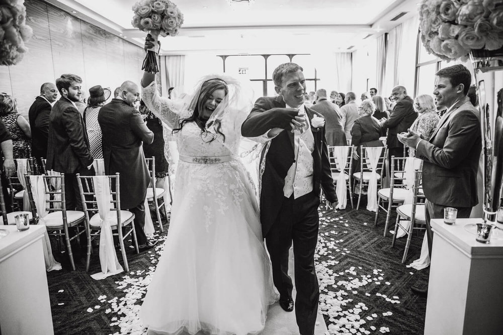 bride and groom celebrate during recessional after marriage service
