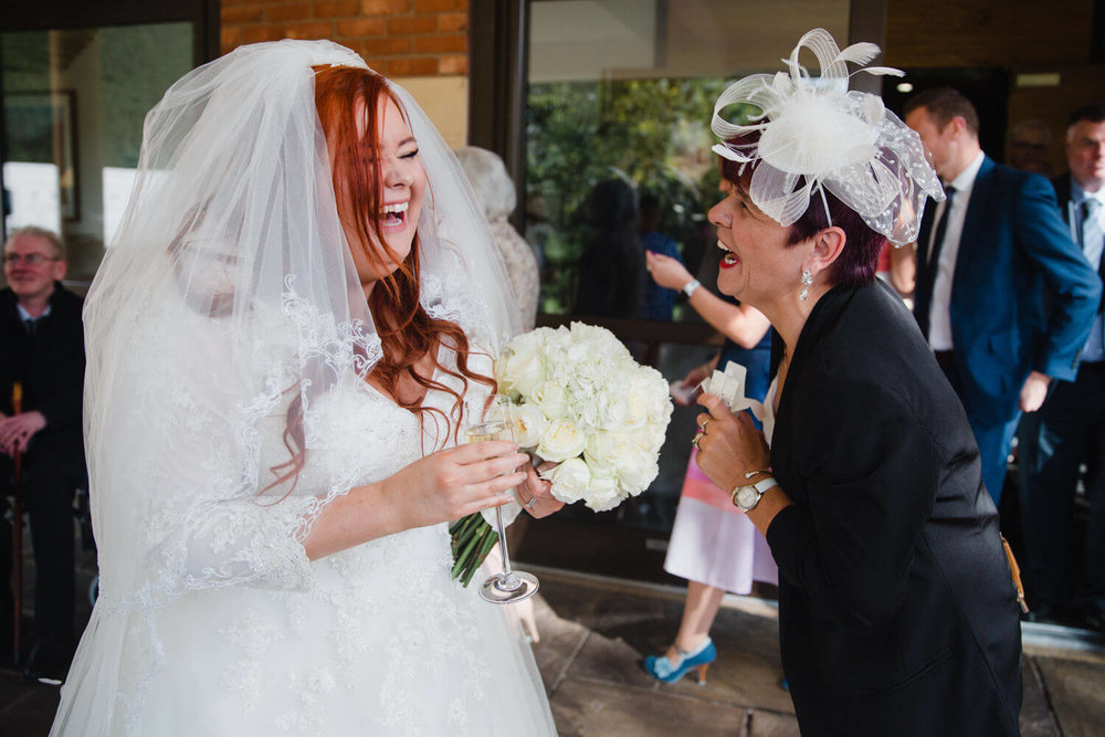 bride laughing out loud with wedding guest