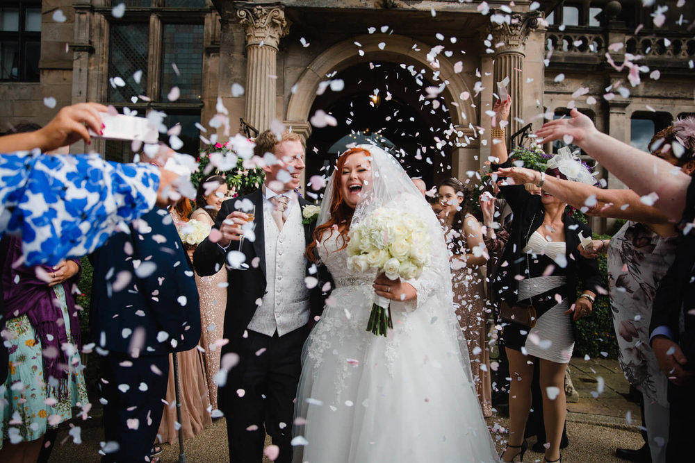 large shower of confetti thrown outside old building idyllic backdrop