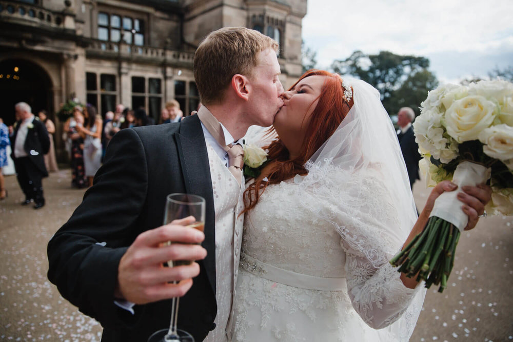 bride and groom kiss after confetti throwing