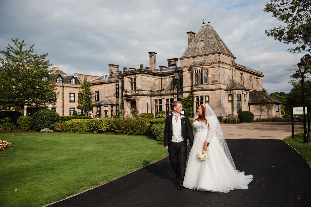 wide angle lens photograph of bride and groom walking down path in front of rookery hall