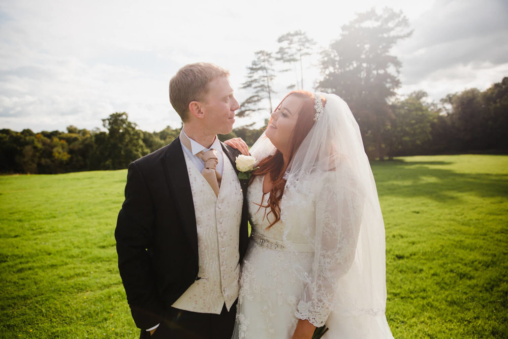 close up of newlyweds in field with sun flare from horizon