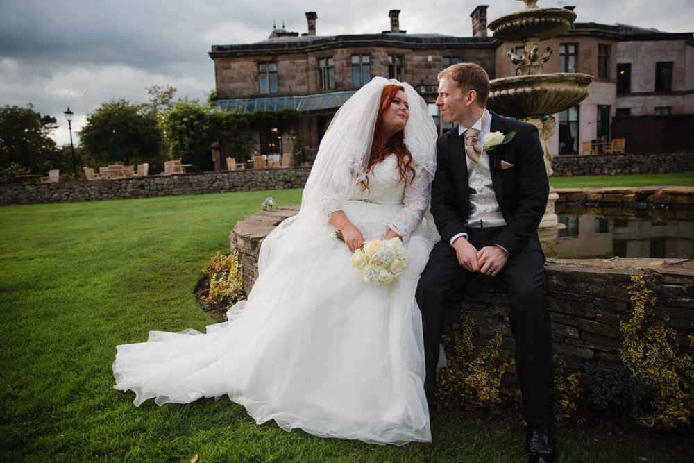 bride and groom sat on fountain in gardens of rookery hall
