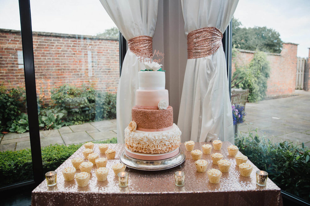 wide angle photograph of wedding cake and cupcake display table