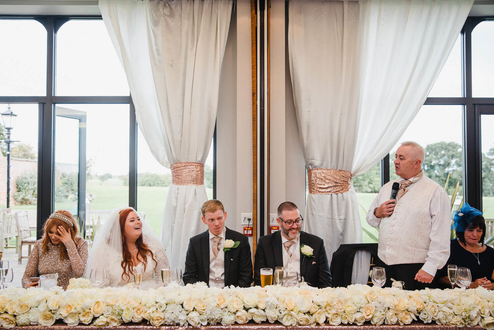 top table of speeches with father of bride delivering to groom