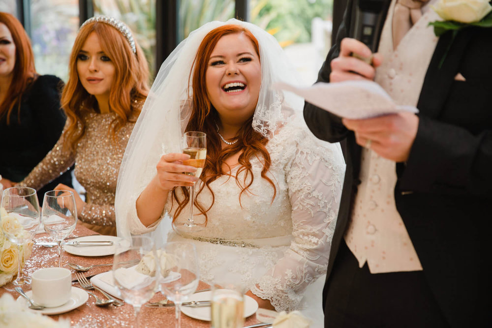 bride sat on top table laughing at grooms speech with champagne flute in hand