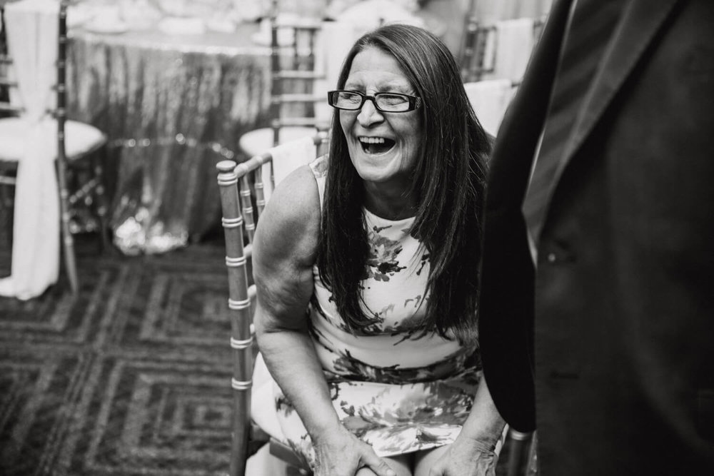 wedding guest sat in chair laughing hysterically at speech