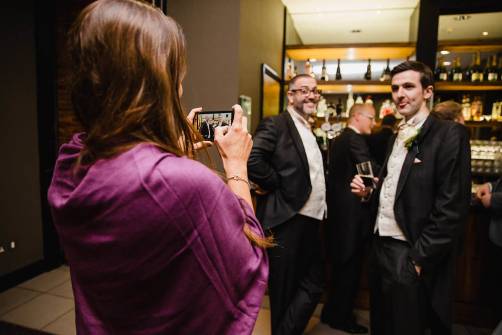 wedding guest taking a photograph of groomsmen stood at bar