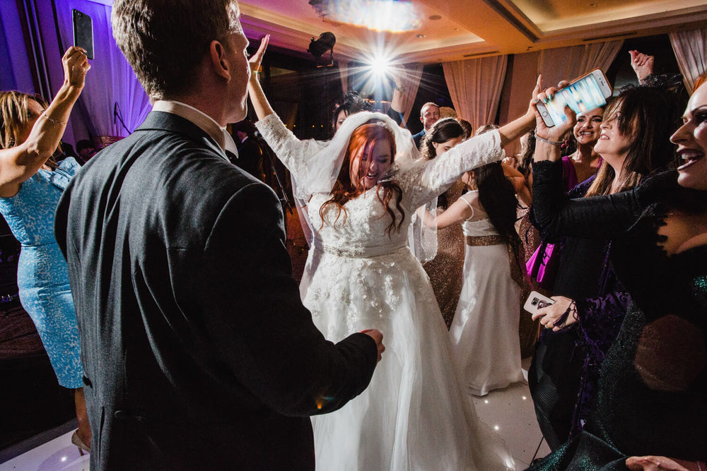 bride dancing on floor with friends and family