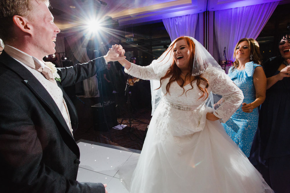 bride and groom holding hands on the dancefloor
