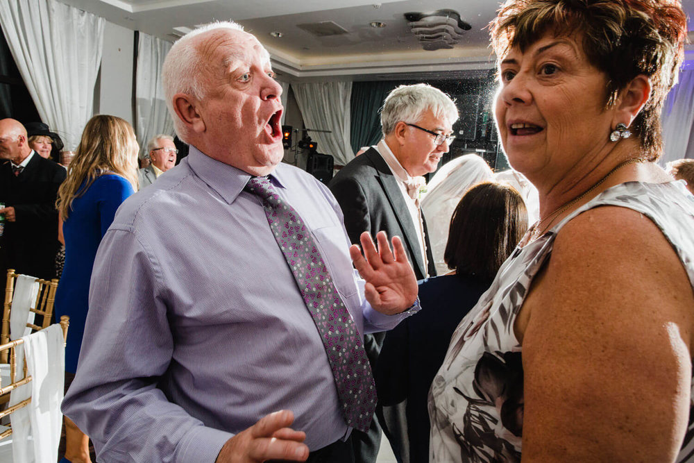 uncle with open mouthed expression singing to wife on dance floor