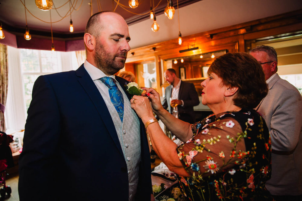 groomsman having pin-hole flower fixed to lapel of suit