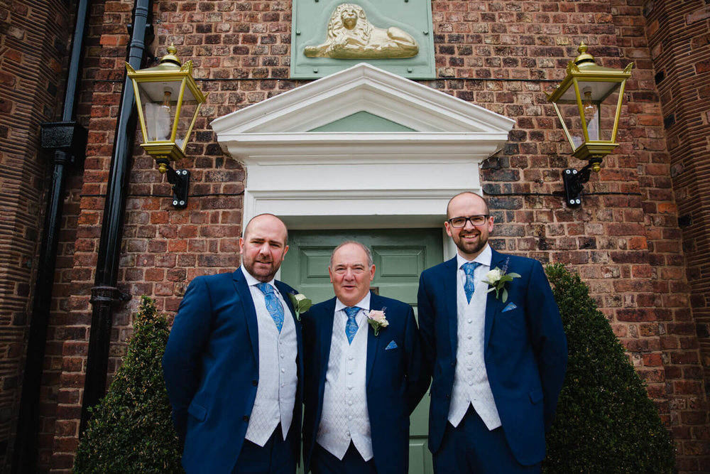 groom and groomsmen portrait in entrance lobby doorway