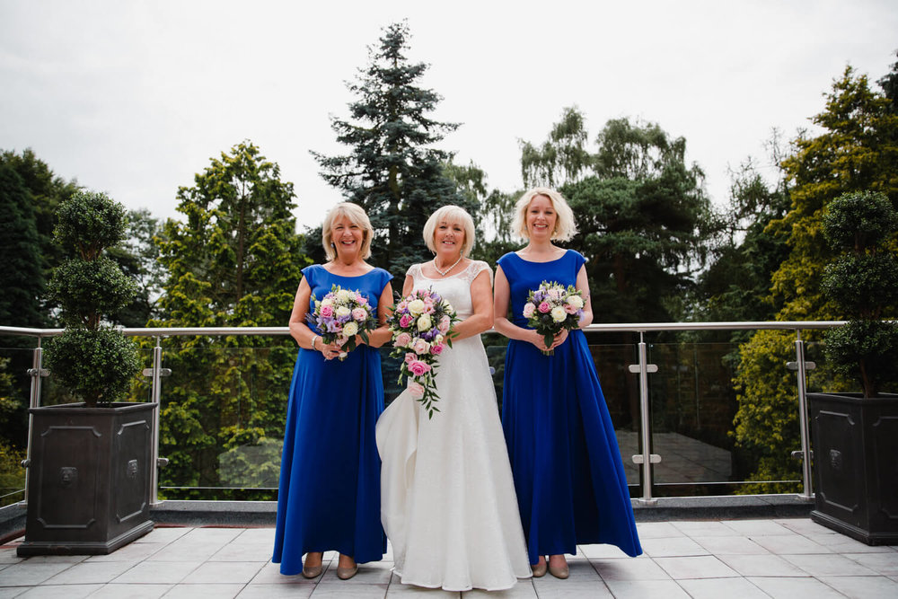 full length portrait of bride and bridesmaids on balcony