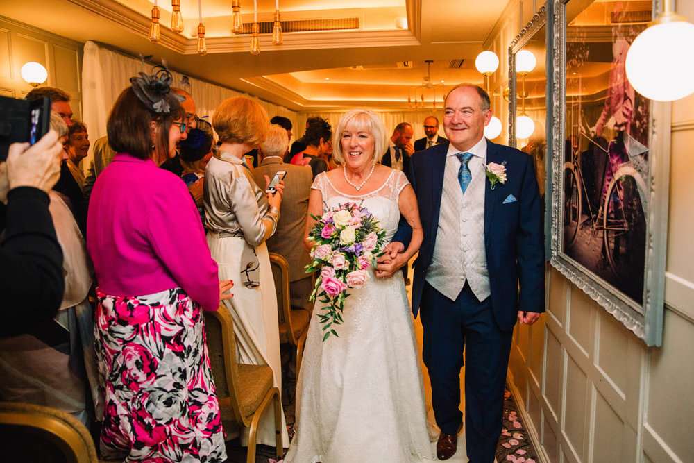 wedding service recessional as newlyweds link arms whilst walking down the aisle