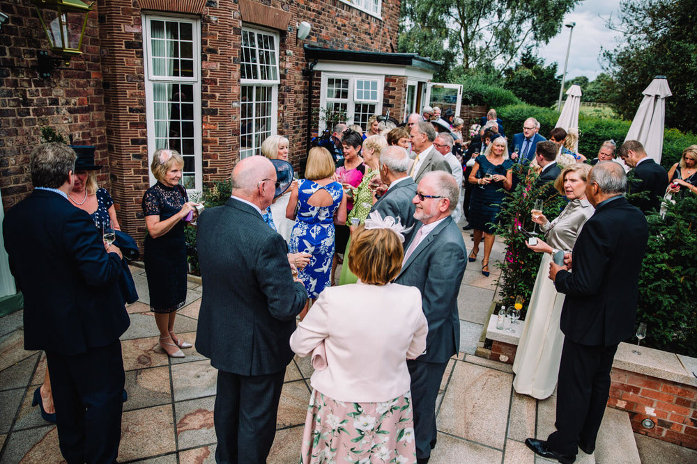 wide angle photograph of all wedding guests enjoying cocktail drinks in gardens