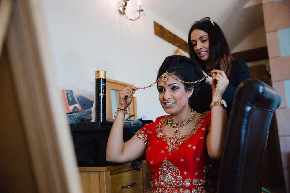 Bride attaching tiara jewellery to head